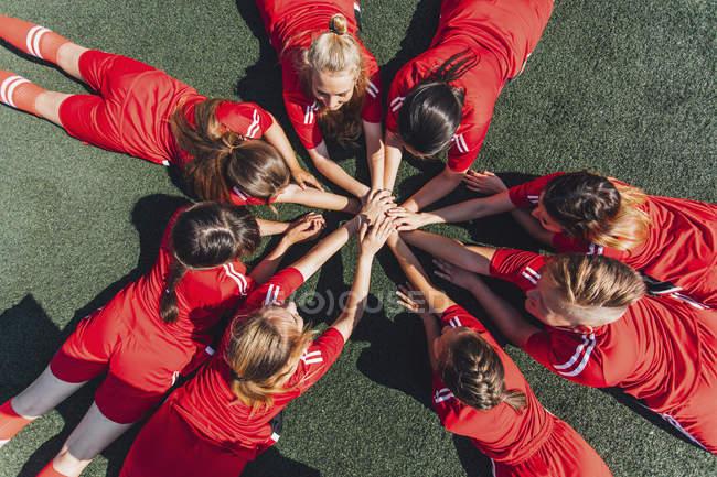 Visão de alto ângulo da equipe de esportes empilhando as mãos em campo — Fotografia de Stock