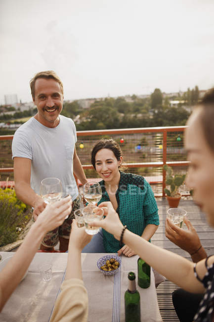 Happy friends toasting wineglasses at outdoor table on patio — Stock Photo