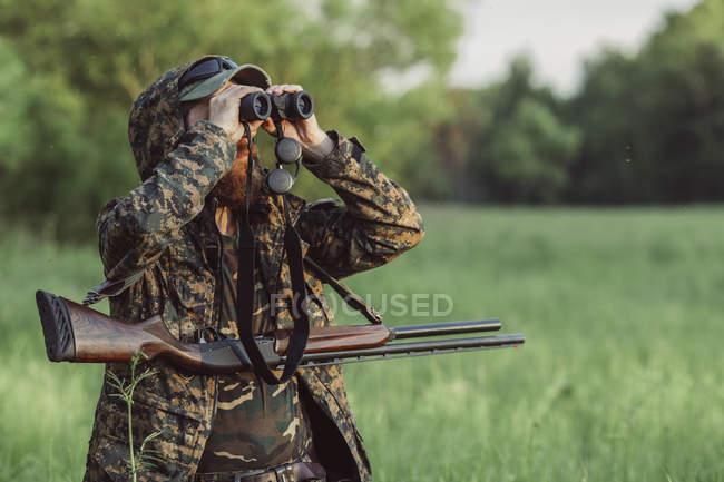 Cazador busca a través de binoculares en campo de hierba - foto de stock