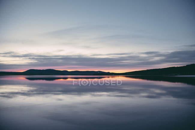 Idílica vista del lago y las montañas en silueta contra el cielo dramático al atardecer - foto de stock