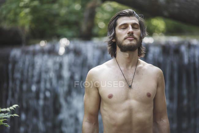 Jovem sem camisa com os olhos fechados em pé contra a cachoeira — Fotografia de Stock