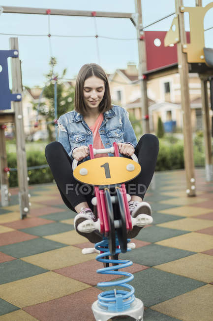 Smiling woman sitting on spring ride in park — Stock Photo