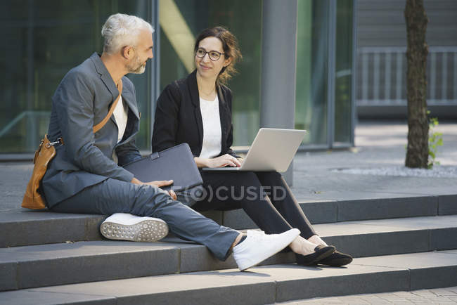 Business coworkers with laptop discussing while sitting on steps in city — Stock Photo