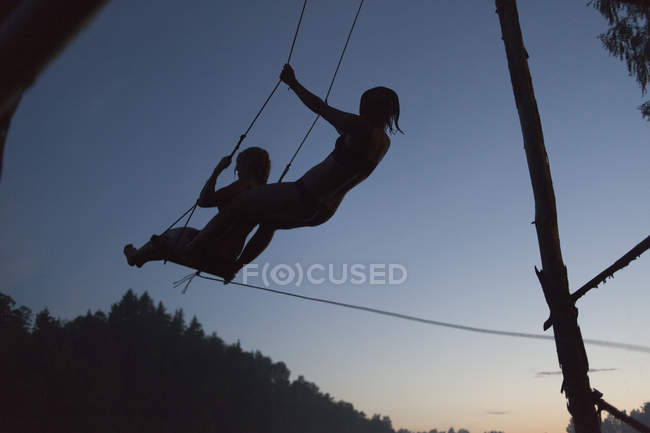 Low angle view of silhouetted women swinging against clear sky during sunset — Stock Photo