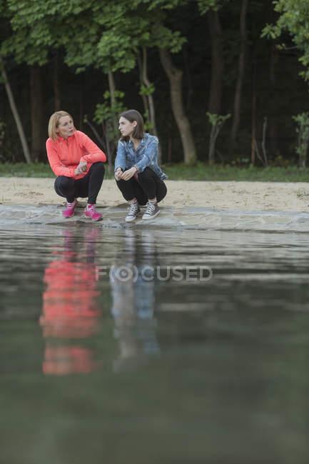 Mutter und Tochter reden, während sie in der Natur am Ufer des Sees hocken — Stockfoto
