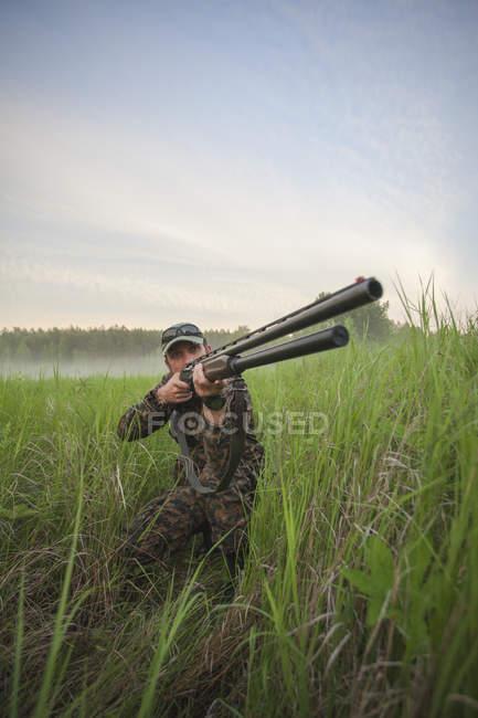 Rifle de puntería de cazador en campo contra el cielo - foto de stock