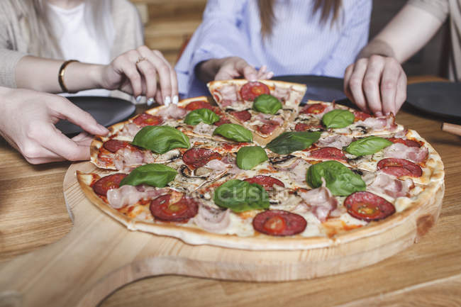 Cropped image of friends having pizza at restaurant — Stock Photo