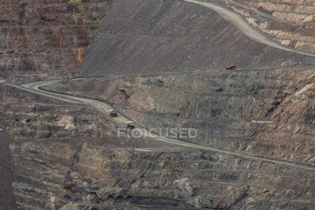 Vue en angle élevé des camions à benne sur le chemin de terre à la mine de charbon à ciel ouvert — Photo de stock