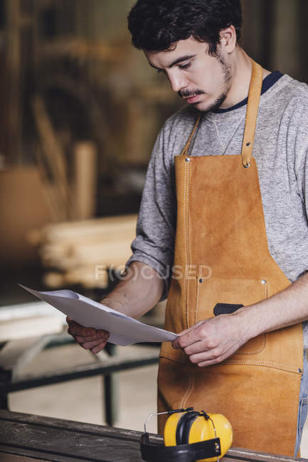 Young carpenter reading document at workshop — Stock Photo