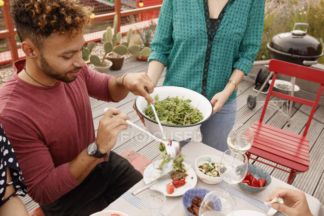Young man serving salad in plate at patio — Stock Photo