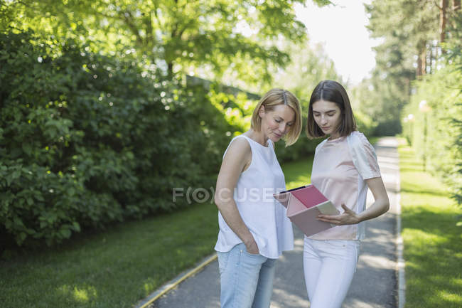 Daughter showing digital tablet to mother while standing on footpath in park — Stock Photo