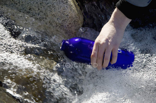 Crop male hand filling drink bottle in river — Stock Photo