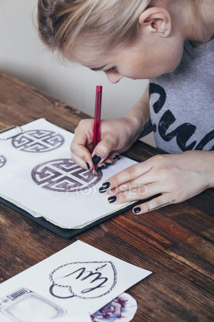 Close-up of tattoo artist drawing designs at art studio — Stock Photo