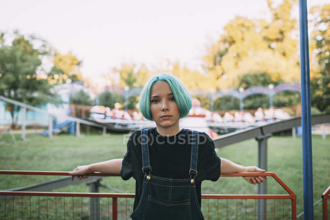 Portrait of teenage girl standing by railing at amusement park — Stock Photo