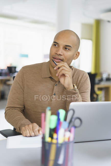 Thoughtful businessman sitting with laptop in creative office and looking away — Stock Photo
