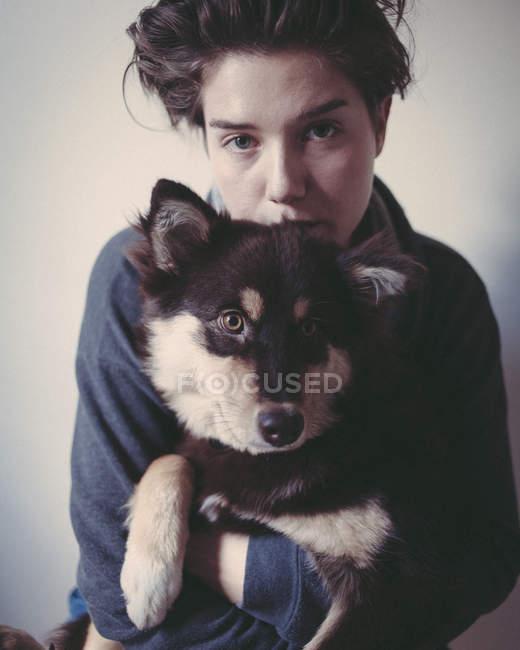 Портрет уверенной женщины, обнимающей собаку на сером фоне — стоковое фото