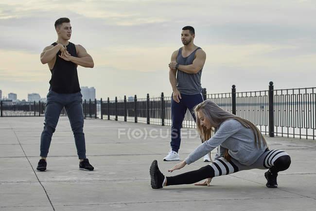 Юные спортсмены, растянувшиеся на набережной на закате — стоковое фото