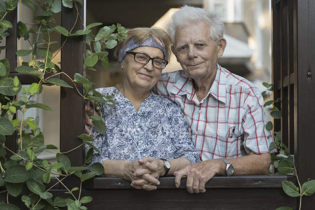 Портрет улыбающейся пожилой пары, стоящей у окна — стоковое фото