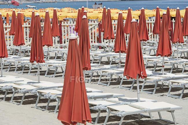 Fechado vermelhos guarda-sóis e espreguiçadeiras na praia — Fotografia de Stock