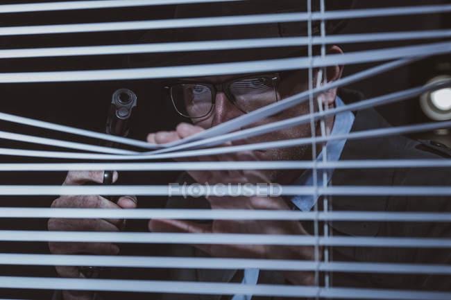 Giovane uomo con pistola sbirciare attraverso le tende della finestra — Foto stock