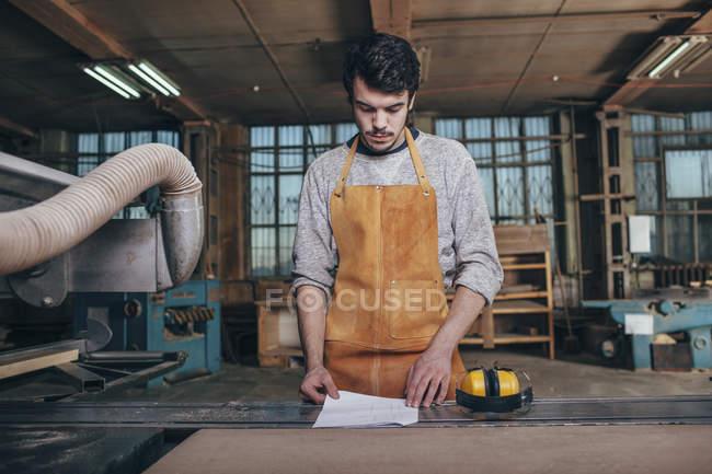 Documento de leitura do carpinteiro no banco na oficina — Fotografia de Stock