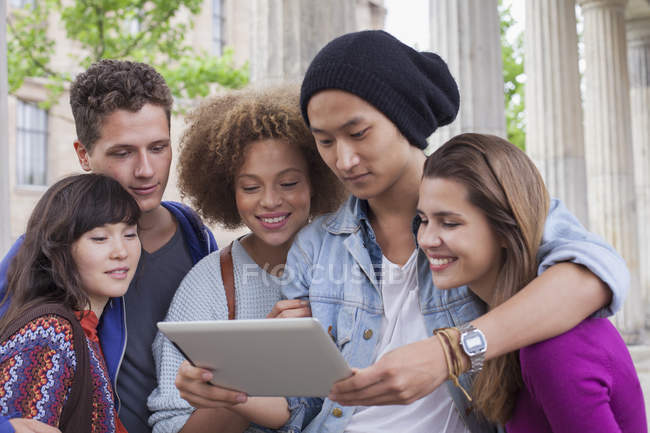 Young man showing digital tablet to multi-ethnic friends — Stock Photo
