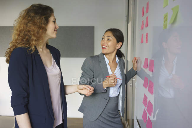 Business people discussing over adhesive notes in creative office — Stock Photo