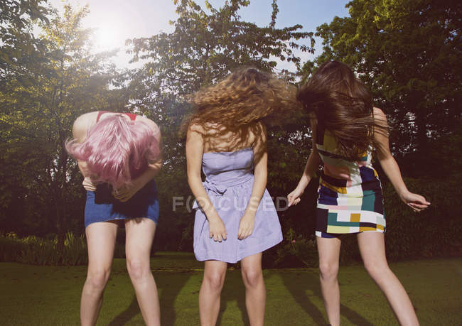 Excited female friends tossing hair at yard during sunny day — Stock Photo