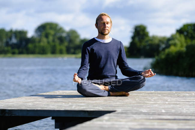 Mature man practicing lotus position on pier by lake against sky — Stock Photo