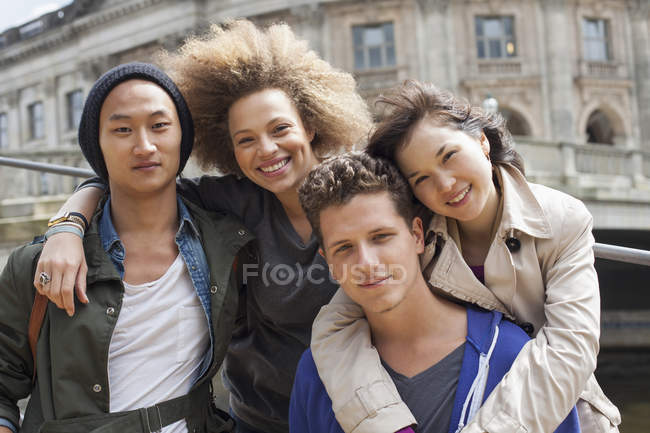 Low angle portrait of smiling young multi-ethnic friends against Bode Museum, Berlin, Germany — Stock Photo