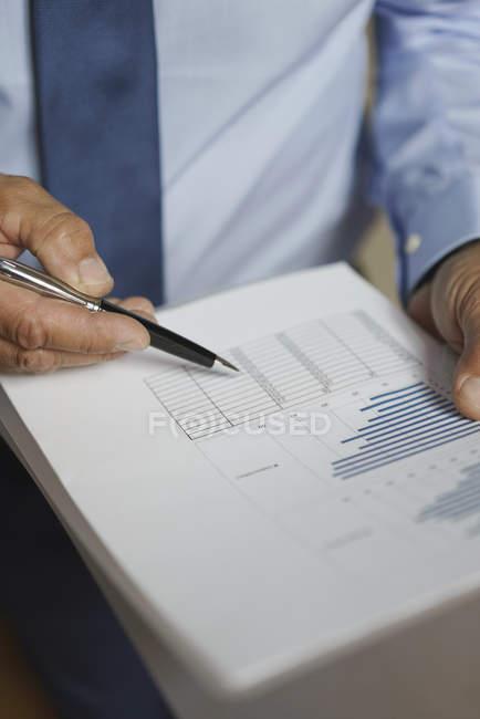 Parte centrale dell'uomo d'affari analizzando documenti grafico — Foto stock