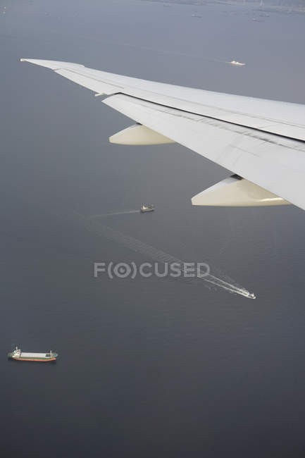 Cropped image of aircraft wing over sea with ships — Stock Photo