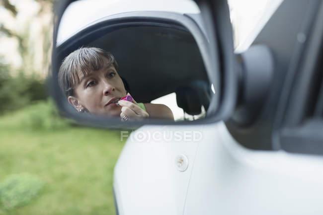 Frau trägt Lippenstift auf, während sie in den Seitenspiegel des Autos blickt — Stockfoto
