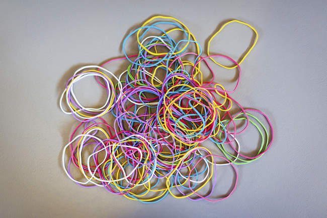 Directly above shot of multi colored rubber bands on gray background — Stock Photo