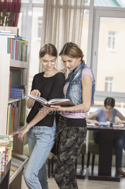 Smiling friends reading book by bookshelf with woman studying in background — Stockfoto