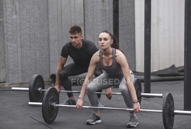 Male and female athlete exercising with barbells during crossfit training — Stock Photo