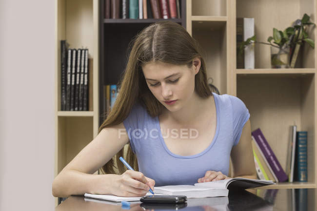 Serious student writing on book while sitting against bookshelf at library — Photo de stock