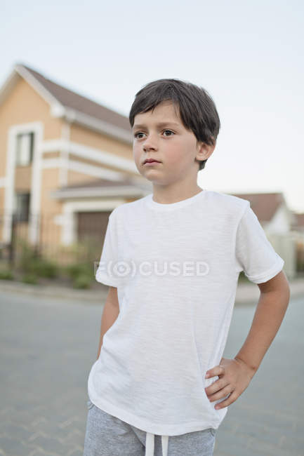 Rapaz atencioso de pé com a mão na anca na cidade — Fotografia de Stock