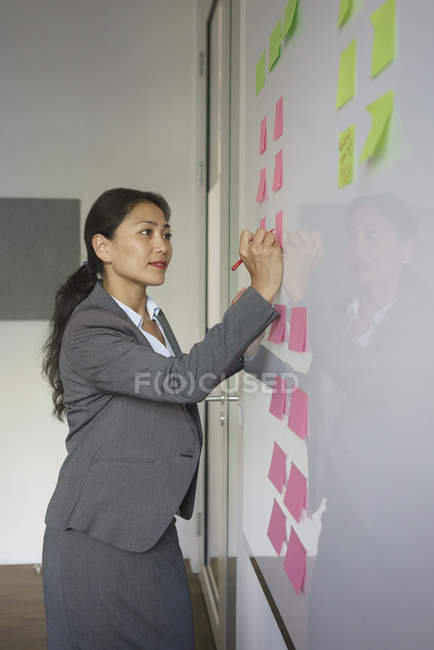 Предприниматель, писать на клей ноте, подключенным через доску в офисе творческих — стоковое фото