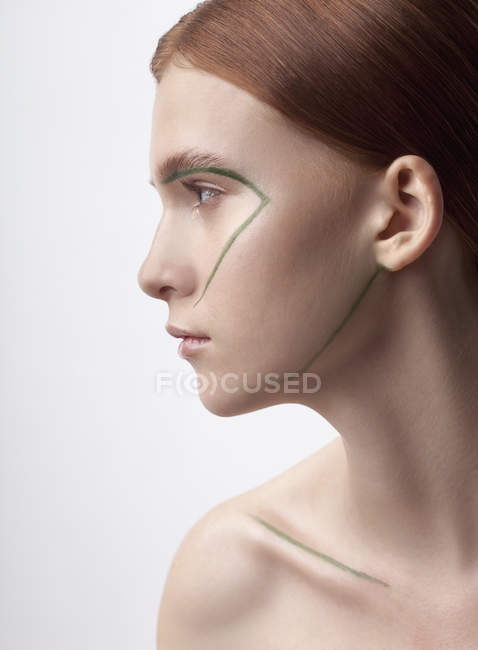 Close-up of topless teenage girl with face paint against white background — Stock Photo