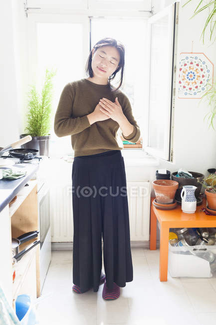 Smiling young woman with hands clasped on heart standing against window — Stock Photo