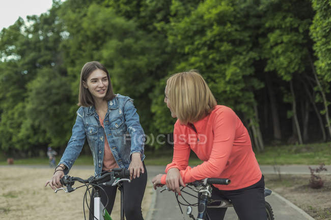 Smiling daughter talking to mother while sitting on bicycle against trees in park — Stock Photo