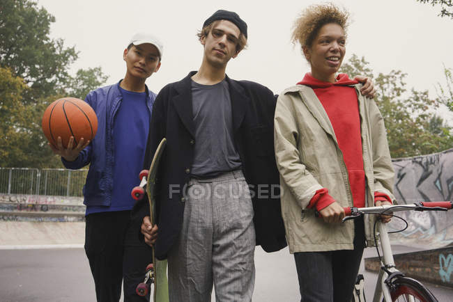 Multi-ethnic friends walking together in skate park with bicycle — Stock Photo
