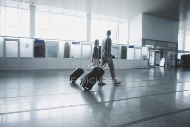 Молодая пара с багажом ходьба в аэропорту — стоковое фото