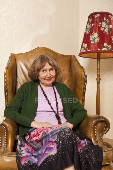 Portrait of senior woman sitting in armchair in living room — Stock Photo