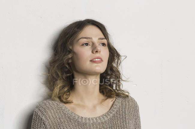 Thoughtful young woman standing against white background — Stock Photo