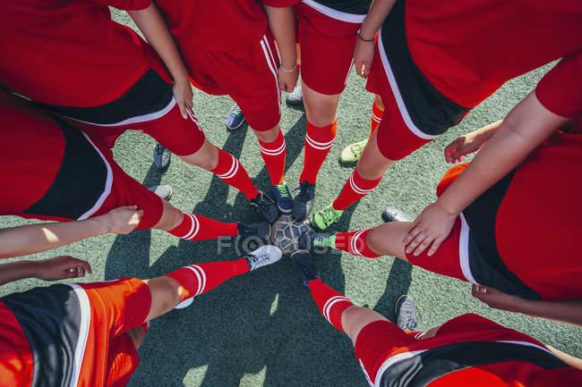 Взгляд сверху вниз на футболистов, касающихся мяча ногами на поле — стоковое фото