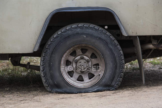 Close-up of vehicle with flat tire on field — Stock Photo