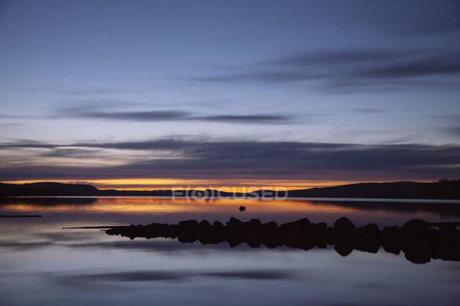 Идиллический вид озера на фоне драматического неба на закате — стоковое фото