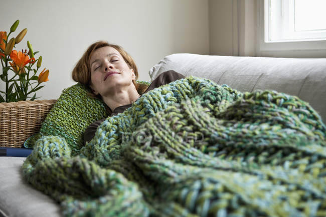 Relaxed mature woman napping on sofa at home at daytime — Stock Photo